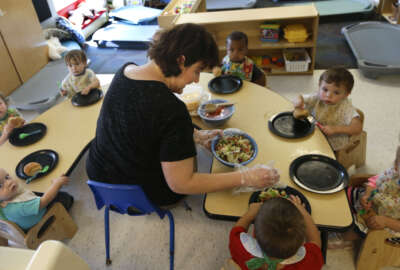 Alyssa Breitmayer feeds her class of one-year-olds at the Olathe Family YMCA in Olathe, Kan., Wednesday, June 24, 2015. As early childhood teachers lament toddlers too large to fit in playground swings, officials are mulling changes designed to make meals served to millions of kids in day care healthier.  (AP Photo/Orlin Wagner)