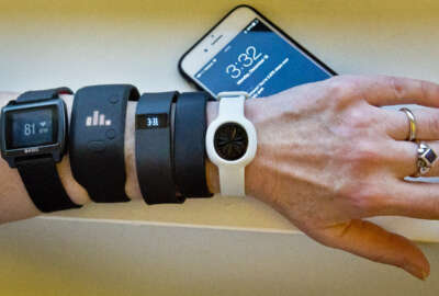 FILE - In this Dec. 15, 2014, file photo, fitness trackers, from left, Basis Peak, Adidas Fit Smart, Fitbit Charge, Sony SmartBand, and Jawbone Move, are posed for a photo next to an iPhone, in New York. Although sales of fitness trackers are strong, many of their owners lose enthusiasm for them once the novelty wears off. (AP Photo/Bebeto Matthews, File)