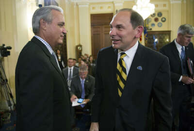 House Veterans Affairs Committee Chairman Jeff Miller, R-Fla., walks past Veterans Affairs Secretary Robert McDonald after a brief chat prior to the Committee's hearing the pending Veterans Affairs health care budget shortfall, on Capitol Hill in Washington, Wednesday, July 22, 2015. (AP Photo/Cliff Owen)