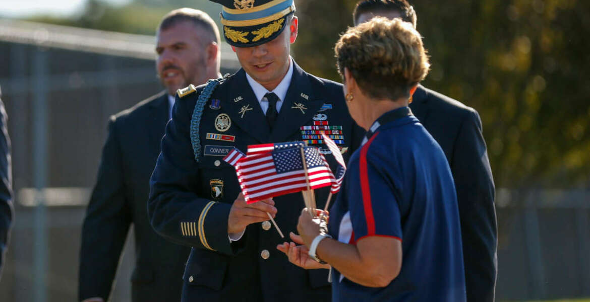 Donna Flinders, United Service Organizations volunteer, hands flags to those attending the funeral service for Army Master Sgt. Corey Hood, Saturday, Aug, 22, 2015, in West Chester, Ohio. Hood, 32, a member of the Army's Golden Knights parachute team, died Aug. 16 following a performance at the Chicago Air and Water Show.  Parachuters fly over Lakota West's football field Saturday, Aug. 21, 2015,  during the funeral service in West Chester, Ohio, for Army Master Sgt. Corey Hood. (Madison Schmidt/The Cincinnati Enquirer via AP)