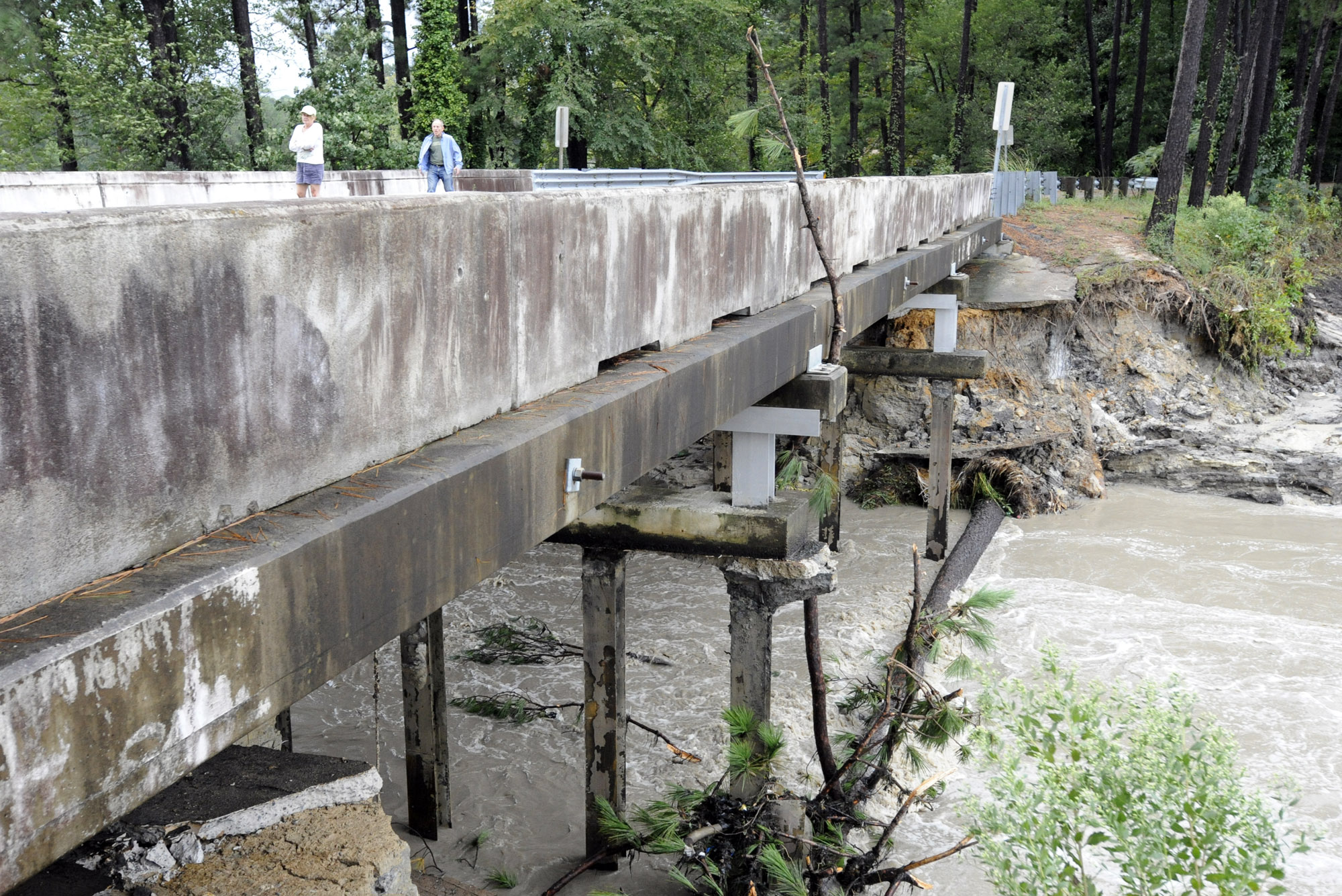 FILE- In this Monday, Oct. 5, 2015 file photo, Residents of a lakeside neighborhood walk across Overcreek Bridge by the remains of a failed dam in Columbia, S.C. Officials say the structure beneath a road collapsed Monday afternoon following days of heavy rain, nearly emptying a lake in a few minutes. No one was injured. South Carolina had problems with crumbling roads and bridges and old drinking water systems and dams long before the historic floods of the past week. Now the state faces what will likely be hundreds of millions if not billions of dollars of bills to fix washed out roads and bridges and destroyed dams. (AP Photo/Jay Reeves, File)