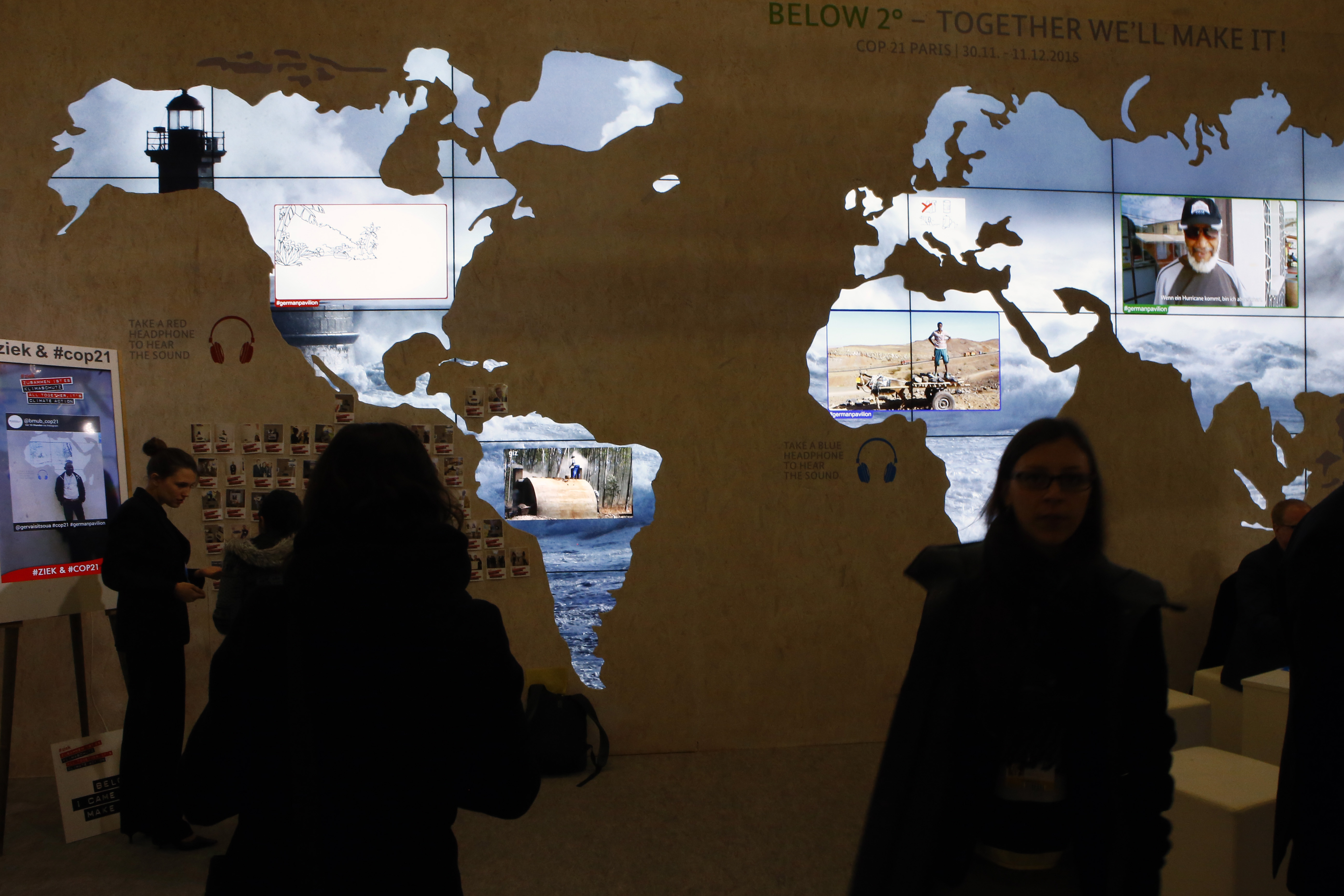 People pass a world map at The German pavillon entitled
