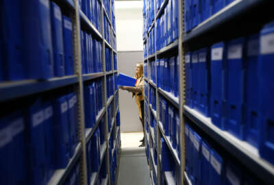 Pascale Etiennette, chief of the Paris Police Prefecture Archives department holds a file box in the controlled storage room where historic documents are stored in Paris, France, Tuesday, Dec. 29, 2015. France is opening police and legal archives from the collaborationist Vichy regime, allowing free access to previously classified documents from World War II. (AP Photo/Francois Mori)