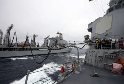Fuel lines connect the USS William P. Lawrence guided missile destroyer, right, with a tanker during a refueling at sea Wednesday, Jan. 20, 2016, in waters off  Coronado, Calif. The U.S. Navy is launching a carrier strike group to be powered partly by biofuel, calling it a milestone toward easing the military's reliance on foreign oil. (AP Photo/Gregory Bull)