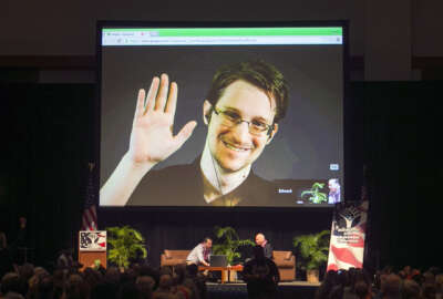 FILE - In this Feb. 14, 2015, file photo, Edward Snowden appears on a live video feed broadcast from Moscow at an event sponsored by ACLU Hawaii in Honolulu. Speaking via Skype from Russia, Snowden told an audience of supporters in New Hampshire on Saturday, Feb. 20, 2016, that he is willing to be extradited to the United States if the federal government would guarantee he would get a fair trial. The former National Security Agency contractor in 2013 leaked details of a secret government eavesdropping program and left the country. He faces U.S. charges that could land him in prison for up to 30 years. (AP Photo/Marco Garcia, File)