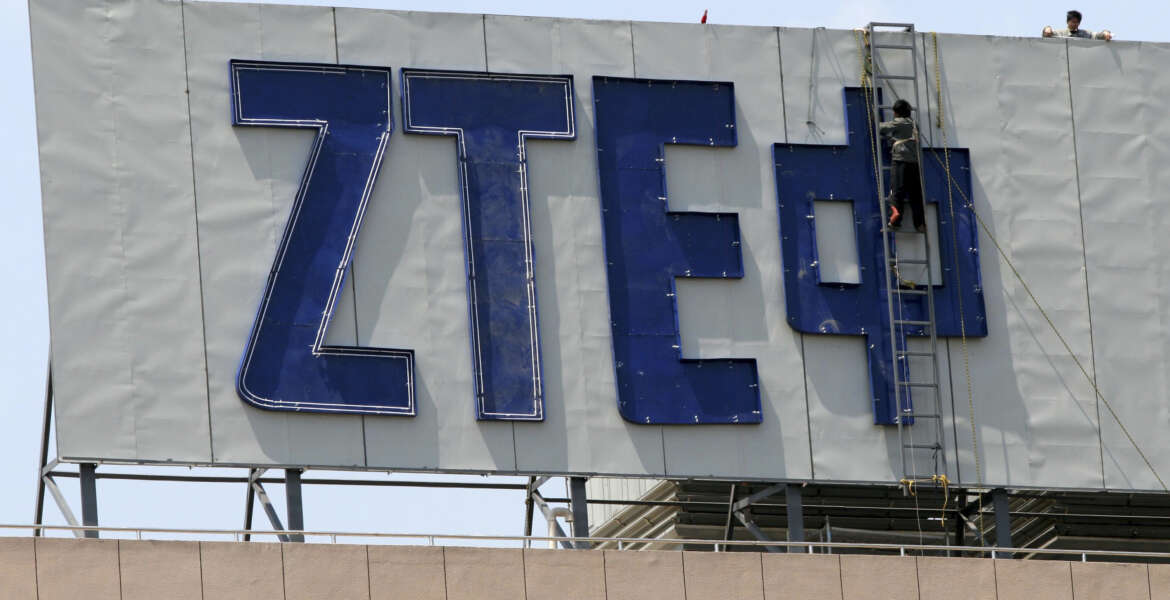 In this April 18, 2007 photo, workers install the logo for ZTE, a leading Chinese communications company, on top of an office building in Nanjing in eastern China's Jiangsu province. Washington has imposed restrictions on the ability of one of China's biggest telecoms equipment makers, ZTE Corp., to use American components after concluding the state-owned company improperly exported U.S. technology to Iran. Sanctions that took effect Tuesday, March 8, 2016, were imposed after ZTE was found to be