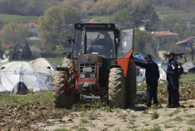 Greek police officers speak with Lazaros Oulis, farmer and owner of fields near the makeshift refugee camp at the northern Greek border point of Idomeni, Greece, Thursday, March 31, 2016. Oulis, tried to plough his land on Thursday, driving the tractor near the  tents and people.(AP Photo/Darko Vojinovic)