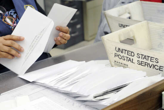 In this Feb. 5, 2016, photo, a mail clerk at the Wynne Unit of the Texas prison system makes her way through a box of letters for inmates in Huntsville, Texas. Every piece of mail is checked for contraband, like drugs hidden under stamps, or messages or words in correspondence that suggest violence or escape plans, as well as attempts by convicts to profit from some enterprise or business while behind bars. (AP Photo/Pat Sullivan)