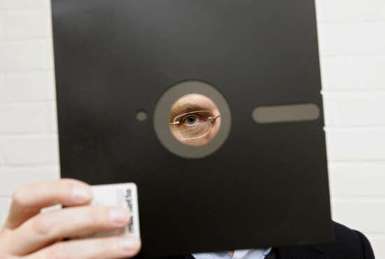 FILE - In this Nov. 16, 2004 file photo, an obsolete 8 and 1-half inch floppy disc  is held in London. Congressional investigators say the government spends about three-fourths of its technology budget maintaining aging computer systems. That includes platforms more than 50 years old in such vital areas as nuclear weapons and Social Security. One still uses floppy disks. (AP Photo/Adam Butler, File)