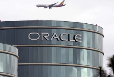 FILE - In this Tuesday, March 20, 2012, file photo, a plane flies over Oracle headquarters in Redwood City, Calif. On Thursday, May 26, 2016, a federal jury sided with Google in a long-running legal battle with tech industry rival Oracle in a complex copyright case that was closely watched in Silicon Valley. Oracle had said Google stole some of its software to create Android, the world's most popular smartphone operating system. Oracle is vowing to appeal. (AP Photo/Paul Sakuma, File)