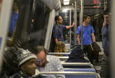 In this Thursday, April 28, 2016 photo, Roger Bowles, center, and Stephen Repetski, center right, ride a blue line Metro train from the McPherson Square Station to Crystal City in Washington. The two are part of a group of hobbyists who monitor the rails for any anomalies or abnormalities and provide real-time info of problems. (Jahi Chikwendiu/The Washington Post via AP) MANDATORY CREDIT
