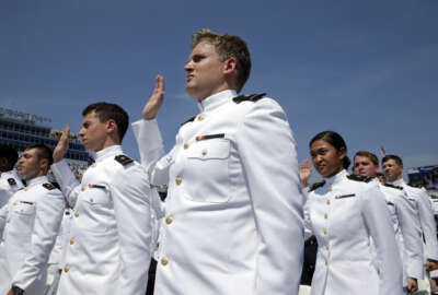 Graduating U.S. Naval Academy Midshipmen raise their right hands as they are commissioned as ensigns in the U.S. Navy during the Academy's graduation and commissioning ceremony in Annapolis, Md., Friday, May 27, 2016. (AP Photo/Patrick Semansky)