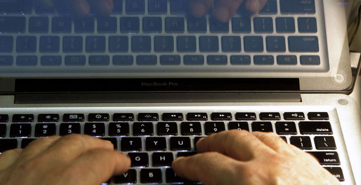 FILE - In this Feb. 27, 2013, file photo, hands type on a computer keyboard in Los Angeles. News that Facebook founder Mark Zuckerberg's rarely used Twitter, LinkedIn and Pinterest accounts were briefly compromised should serve as a reminder that we're all susceptible to hacking. (AP Photo/Damian Dovarganes, File)