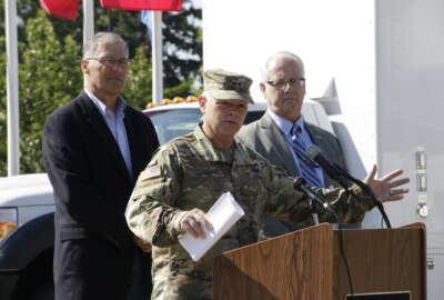 Major General Bret Daugherty, commander of the Washington National Guard, speaks to the media as Washington Gov. Jay Inslee, left, and FEMA Region X Administrator Ken Murphy look on, Tuesday, June 7, 2016, at Camp Murray, Wash.  Washington is participating in a four-day earthquake and tsunami readiness drill in the Pacific Northwest called Cascadia Rising. (AP Photo/Rachel La Corte)