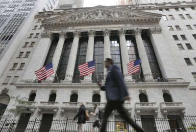 FILE - In this Friday, June 24, 2016, file photo, people walk by the New York Stock Exchange. Global stocks mostly rose Friday, July 1, as authorities stepped in to ease the uncertainty surrounding the British vote to leave the European Union. Investors flocked to equities in the face of narrowing choices for investments amid low or negative interest rates on many bonds. (AP Photo/Richard Drew, File)