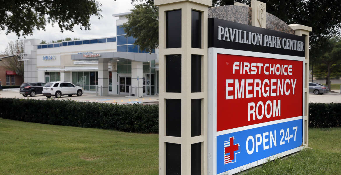 A sign by a nearby road intersection advertises a First Choice Emergency Room, rear, Thursday, Aug. 18, 2016, in Richardson, Texas. Freestanding emergency centers have sprouted in recent years across the suburban landscape, taking root in affluent neighborhoods and directly challenging nearby medical clinics and hospitals.  (AP Photo/Tony Gutierrez)
