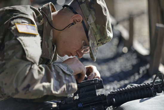 In this photo taken Wednesday, Aug. 17, 2016 U.S. Army Pvt. Austin Lewis adjusts his M-4 weapon's sights while participating in marksmanship training at Fort Jackson, S.C. While some of the Army's newest recruits may have grown up using rifles to hunt or take target practice, the drill sergeants charged with turning 45,000 civilians into warriors every year say more than half may have never touched a gun. (AP Photo/Gerry Broome)