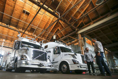FILE - In this Thursday, Aug. 18, 2016, file photo, employees stand next to self-driving, big-rig trucks during a demonstration at the Otto headquarters, in San Francisco. Uber's self-driving startup Otto developed technology allowing big rigs to drive themselves. After taking millions of factory jobs, robots could be coming for a new class of worker: people who drive for a living. (AP Photo/Tony Avelar, File)
