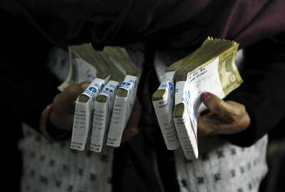 FILE - In this Dec. 16, 2011 file photo, a cashier holds bundles of Indian rupee bank notes at a bank in Allahabad, India. India's prime minister has announced late Tuesday, Nov. 8, 2016, scrapping of high denomination 500 and 1,000 Indian rupees currency notes in what he describes as a major step to fight the menace of black money, corruption and fake currency. Prime Minister Narendra Modi in a speech carried live on radio and television on Tuesday says there is no need to panic as people would be able to deposit these currency notes in their bank account until December 30. (AP Photo/Rajesh Kumar Singh, File)