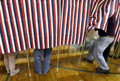 """FILE - In this Nov. 8, 2016 file photo, a voter enters a booth at a polling place in Exeter, N.H. Tweets alone don't make it true. Donald Trump won the presidency earlier this month even as he lost the popular vote to Democrat Hillary Clinton, according to The Associated Press's vote-counting operation and election experts. Trump nonetheless tweeted on Nov. 26 that he won the popular vote. and alleged there was """"serious voter fraud"""" in California, New Hampshire and Virginia. There's no evidence to back up those claims. (AP Photo/Elise Amendola, File)"""
