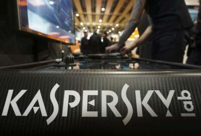 A Kaspersky employee shuffles tokens around a table-top display at the company's stand at a cybersecurity conference in Lille, northern France, Wednesday, Jan. 25, 2017. Kaspersky on Wednesday confirmed that a senior manager at the firm had been arrested in Moscow. (AP Photo/Raphael Satter)