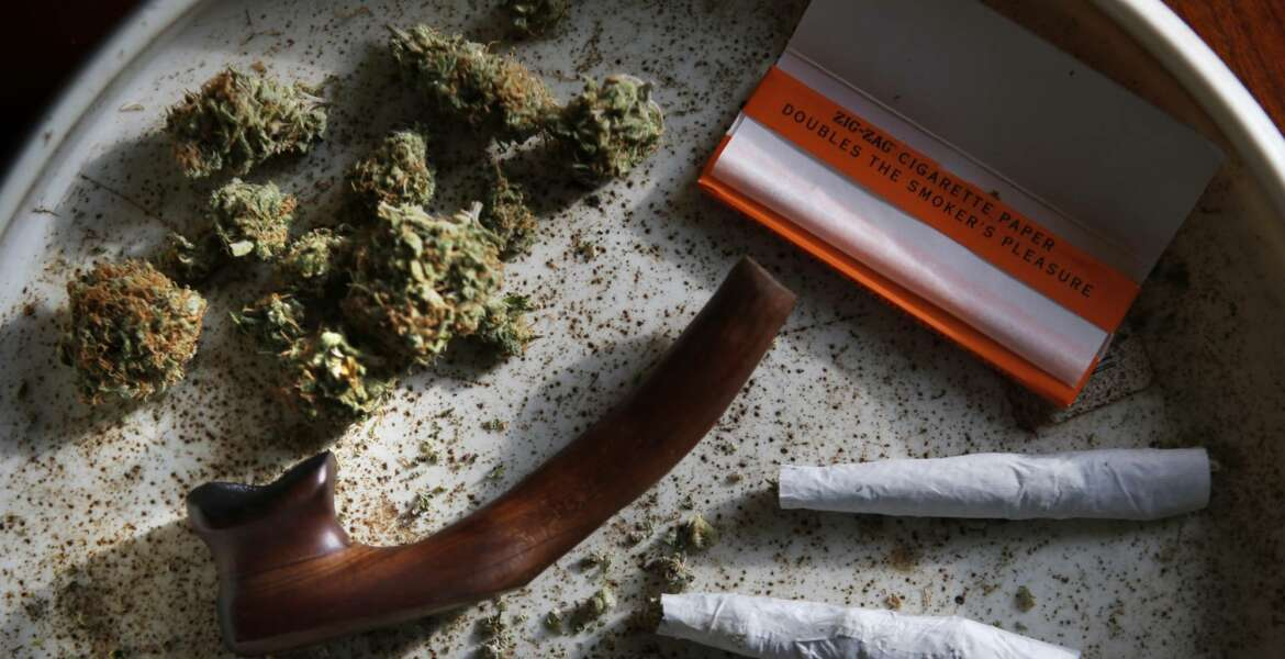 FILE - This this Nov. 21, 2014, file photo shows medical marijuana, a pipe, rolling papers and two joints in Belfast, Maine. The first tangible results of state voters' decision to legalize marijuana are being felt as possession and home growth of marijuana becomes legal Monday, Jan. 30, 2017. Voters narrowly passed the ballot question in November, and the waiting period between the vote and legalization has expired. (AP Photo/Robert F. Bukaty, File)