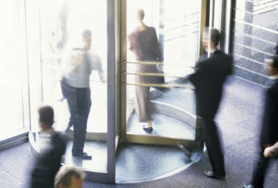 High angle view of business executives walking through a revolving door