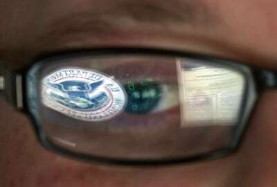 FILE - In this Sept. 30, 2011, file photo, a reflection of the Department of Homeland Security logo is seen reflected in the glasses of a cyber security analyst in the watch and warning center at the Department of Homeland Security's secretive cyber defense facility at Idaho National Laboratory in Idaho Falls, Idaho. Through history, the United States has relied on its borders and superior military might to protect against and deter foreign aggressors. But a lack of boundaries and any rulebook in cyberspace has increased the threat and leveled the playing field today. (AP Photo/Mark J. Terrill, File)