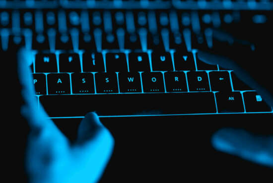 Hacker typing on the illuminated  keyboard by night. Internet safety concept.