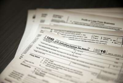 In this Jan. 14, 2017, photo, tax forms sit on a desk at the start of the tax season rush, inside the offices of tax preparation firm Infinite Tax Solutions, in Boulder, Colo. Filing taxes early could speed your return and protect your identity. (AP Photo/Brennan Linsley)