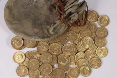 An undated handout photograph, taken at an unknown location, shows part of a hoard of gold coins, made between 1847 and 1915, discovered hidden in an upright piano made by Broadwood & Sons of London and sold to a music establishment in Essex, England, in 1906. British officials are trying to trace the owner of a trove of gold coins worth a