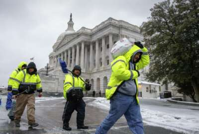 Workmen clear snow on Capitol Hill in Washington, Tuesday, March, 14, 2017. A late-season storm is dumping a messy mix of snow, sleet and rain on the mid-Atlantic, complicating travel, knocking out power and closing schools and government offices around the region.  (AP Photo/J. Scott Applewhite)