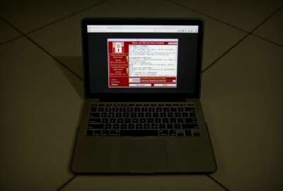 A screenshot of the warning screen from a purported ransomware attack, as captured by a computer user in Taiwan, is seen on laptop in Beijing, Saturday, May 13, 2017. Dozens of countries were hit with a huge cyberextortion attack Friday that locked up computers and held users' files for ransom at a multitude of hospitals, companies and government agencies. (AP Photo/Mark Schiefelbein)
