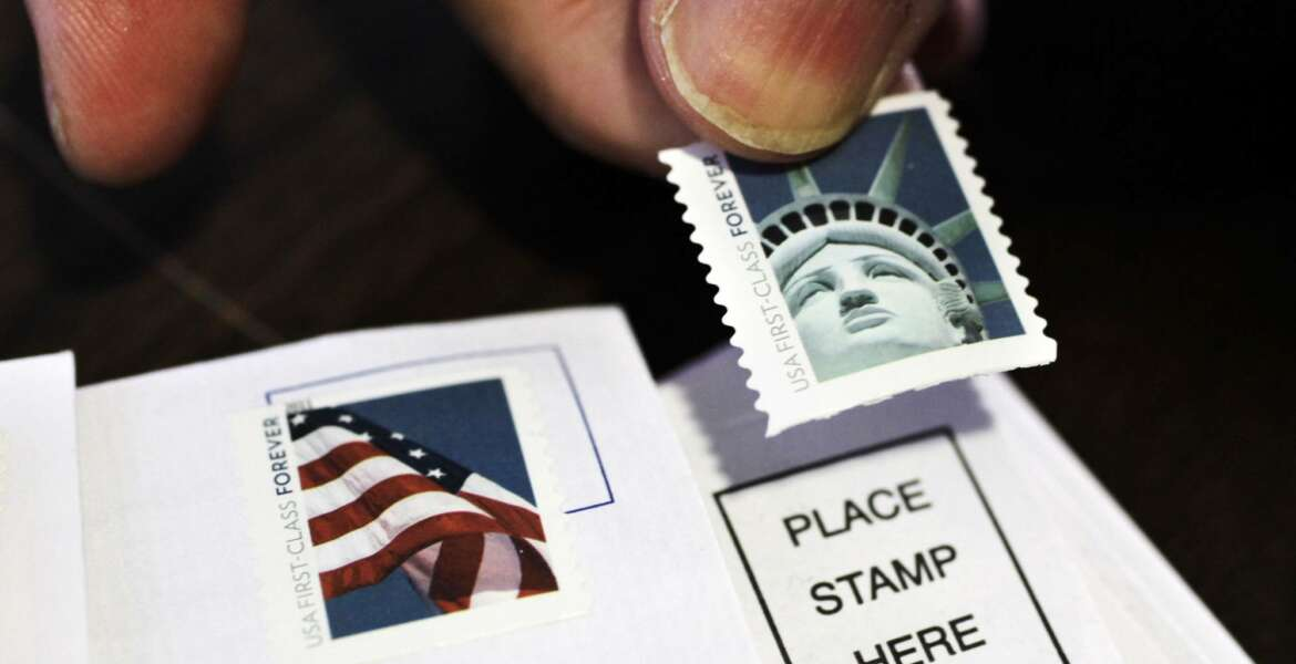 FILE - In this Dec. 5, 2011 file photo, a customer places first class stamps on envelopes at a U.S. Post Office in San Jose, Calif. The U.S. Postal Service is hoping it can soon raise stamp prices by a penny or more.  (AP Photo/Paul Sakuma, File)