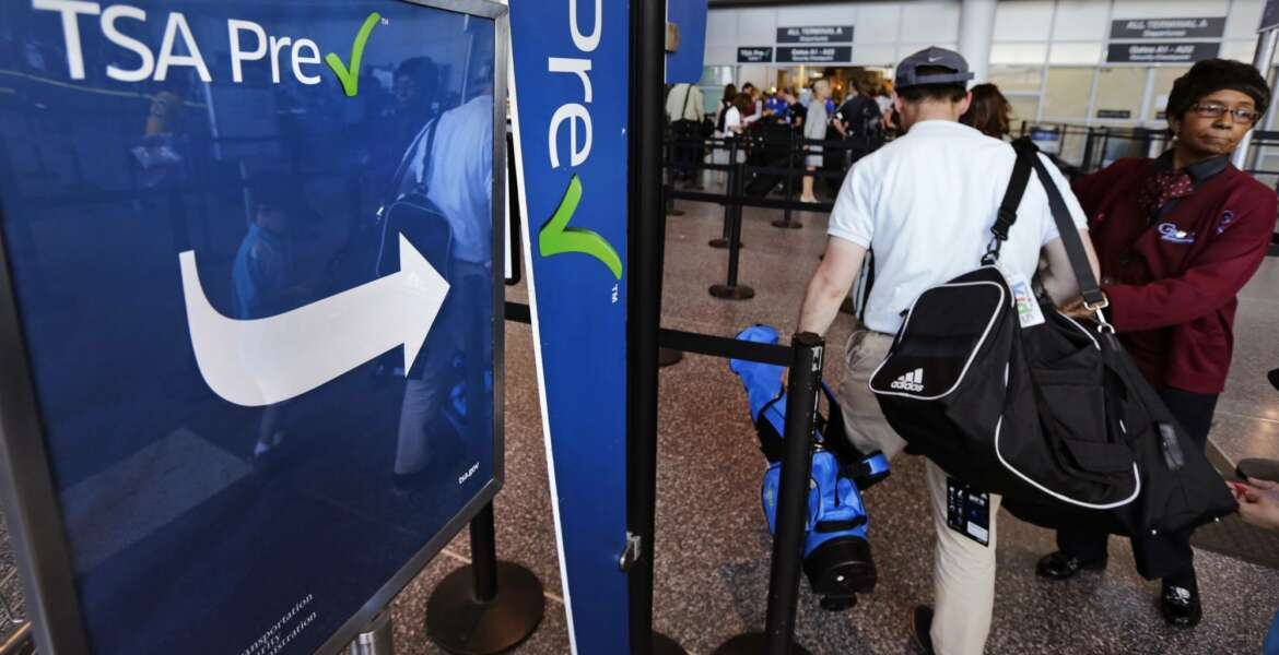 In this Monday, June 27, 2016, photo, a passenger passes by a sign for the Transportation Security Administration's TSA Precheck line in Terminal A at Logan Airport in Boston. By air or car, summer 2017 travel numbers are expected to rise over the previous year thanks to deals on airfares and stable gasoline prices. (AP Photo/Charles Krupa)