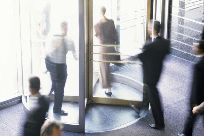 High angle view of business executives walking through a revolving door