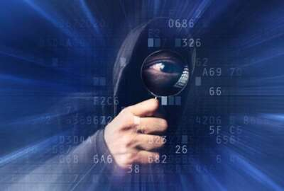 Spyware virus software, bizzare spooky hooded hacker with magnifying glass analyzing computer hexadecimal code, stealing online identity, breaking into personal web accounts.