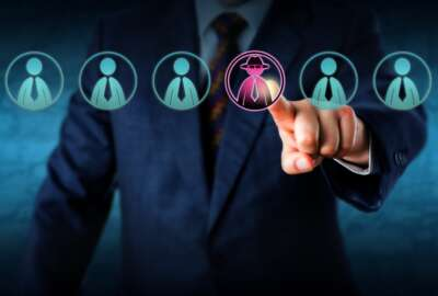 Corporate security manager identifies a potential insider threat in a line-up of eight white collar workers. Hacker or spy icon lights up purple. Cybersecurity and human resources challenge concept.