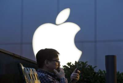FILE - In this Friday, May 13, 2016, file photo, a man uses his mobile phone near an Apple store in Beijing. On Wednesday, July 12, 2017, Apple announced it will open a data center in mainland China with ties to the country's government, raising concerns about the security of iCloud accounts that store personal information transferred from iPhones, iPads and Mac computers there. (AP Photo/Ng Han Guan, File)