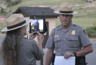 In a Sunday, July 16, 2017 photo, Justin Cawiezel, chief ranger at the Scotts Bluff National Monument, listens to questions from students in Afghanistan while Park Ranger Lesley Gaunt, lead interpreter, makes sure students and Cawiezel can see and hear each other. Park Superintendent Dan Morford, lead interpreter Lesley Gaunt and Chief Ranger Justin Cawiezel were at the Scotts Bluff National Monument on Sunday to give more than 60 Afghan students a virtual tour through an iPad. (Irene North/The Star-Herald via AP)