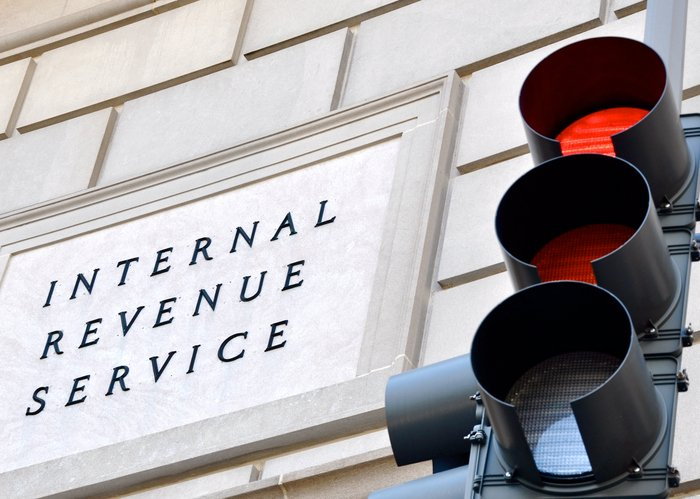 Internal Revenue Service sign with a traffic signal in the foreground indicating a red light.