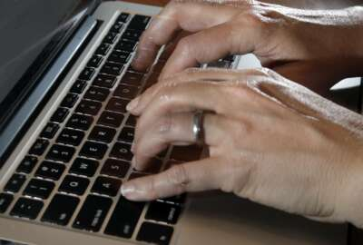 In this Monday, June 19, 2017, photo, a person types on a laptop keyboard, in North Andover, Mass. The American workplace is grueling, stressful and surprisingly hostile. So finds an in-depth study of 3,066 U.S. workers, released Monday, Aug. 14, 2017, by the Rand Corp., Harvard Medical School and the University of California, Los Angeles. (AP Photo/Elise Amendola)