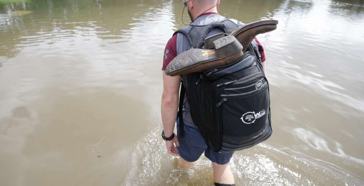 CORRECTS CREDIT - Danny Hannon carries his dry boots in his backpack as he goes to check his home in the aftermath of Harvey, Wednesday, Aug. 30, 2017 in Houston. Harvey's floodwaters started dropping across much of the Houston area, but many thousands of homes in and around the nation's fourth-largest city were still swamped and could stay that way for days or longer. (Melissa Phillip/Houston Chronicle via AP)
