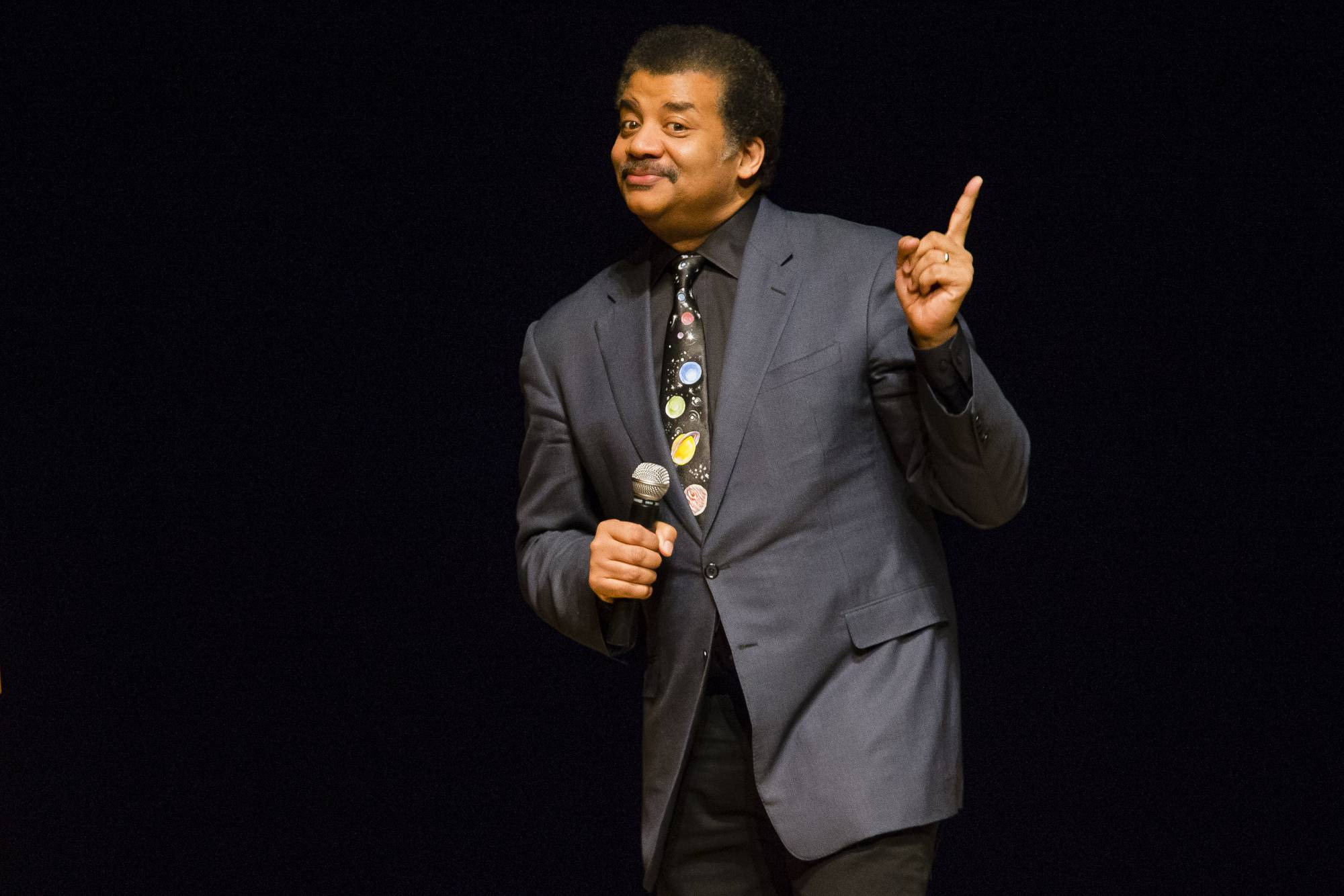 FILE - In this March 21, 2017 file photo, astrophysicist Neil deGrasse Tyson presents a lecture at the Morris Performing Arts Center in South Bend, Ind. Tyson has a suggestion for anyone with a view of next week's solar eclipse: Put down your smartphone and take in the phenomenon yourself. Tyson told an audience to
