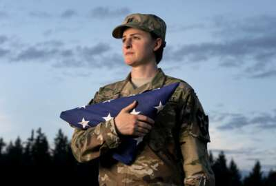 FILE - In this Aug. 28, 2015 file photo, Capt. Jennifer Peace holds a flag as she stands for a photo near her home in Spanaway, Wash. Peace has been been deployed around the world, including Iraq and Afghanistan. When an officer suggested she leave the military rather than deal with the fallout of being a transgender soldier, Peace was taken aback.