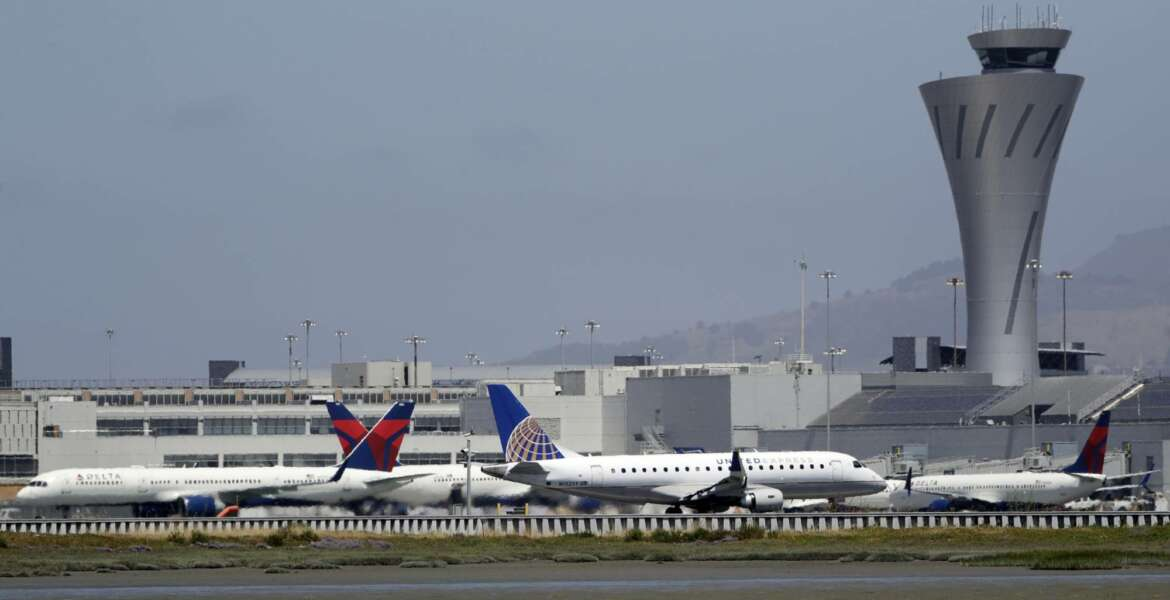 FILE - In this July 11, 2017 file photo, departing and parked aircraft intersect at San Francisco International Airport in San Francisco. Federal officials are imposing new rules on nighttime landings at San Francisco airport after a close call last month. The FAA will also require 2 controllers in the tower. The changes come after an Air Canada jet narrowly missed planes on the ground before aborted an off-line landing on July 7, 2017. (AP Photo/Marcio Jose Sanchez, File)