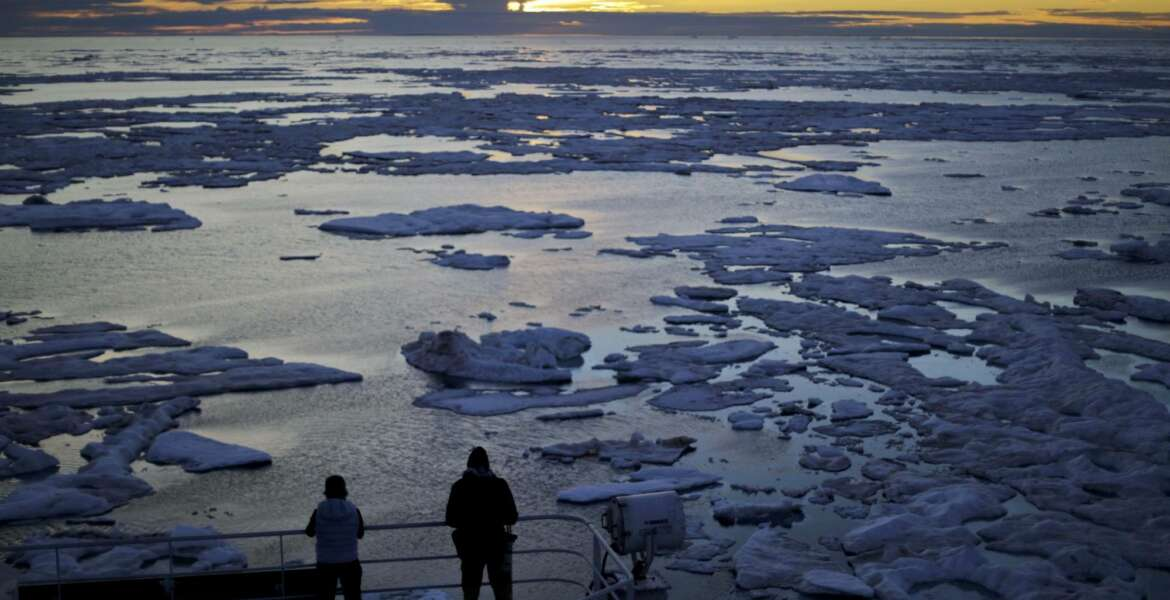 FILE - In this July 21, 2017 file photo, researchers look out from the Finnish icebreaker MSV Nordica as the sun sets over sea ice floating on the Victoria Strait along the Northwest Passage in the Canadian Arctic Archipelago. Studies show the Arctic is heating up twice as fast as the rest of the planet. Scientists are concerned because impacts of a warming Arctic may be felt elsewhere. (AP Photo/David Goldman, File)