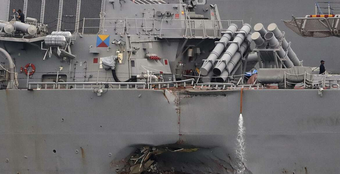 FILE - In this Aug. 22, 2017 file photo. the damaged port aft hull of the USS John S. McCain is visible while docked at Singapore's Changi naval base in Singapore. The wrenching deaths of sailors, drowned while trapped in their bunks on the USS John S. McCain has reverberated around the American fleet.  (AP Photo/Wong Maye-E, File)