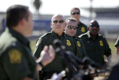 Roy Villarreal, acting Chief Patrol Agent of the Border Patrol, San Diego Sector, left, speaks during a news conference as other Border Patrol agents look on in front of secondary fencing along the border separating San Diego from Tijuana, Mexico, Tuesday, Sept. 26, 2017, in San Diego. The federal government said Tuesday that contractors began building eight prototypes of President Donald Trump's proposed border wall with Mexico, hitting a milestone toward a key campaign pledge. (AP Photo/Gregory Bull)