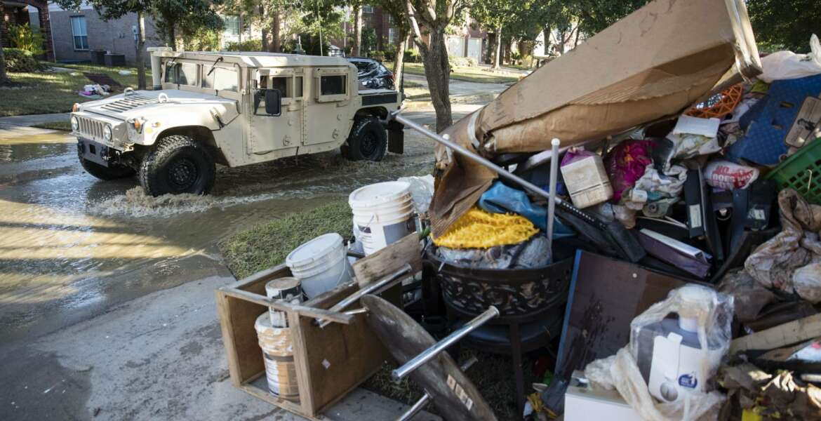 A military vehicle pass flood damaged belongings piled on a homeowners front lawn in the aftermath of Hurricane Harvey on Thursday, Sept. 7, 2017, at the Canyon Gate community in Katy, Texas. (AP Photo/Matt Rourke)